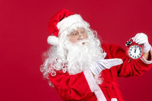 赤い床のクリスマスの休日の新年に時計を保持している正面のサンタクロース