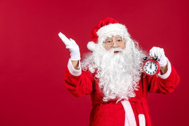 赤い床のクリスマスの新年の感情の休日に時計を保持している正面のサンタクロース