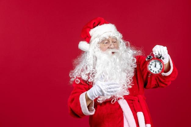 赤いクリスマスの休日の新年の感情に時計を保持している正面のサンタクロース