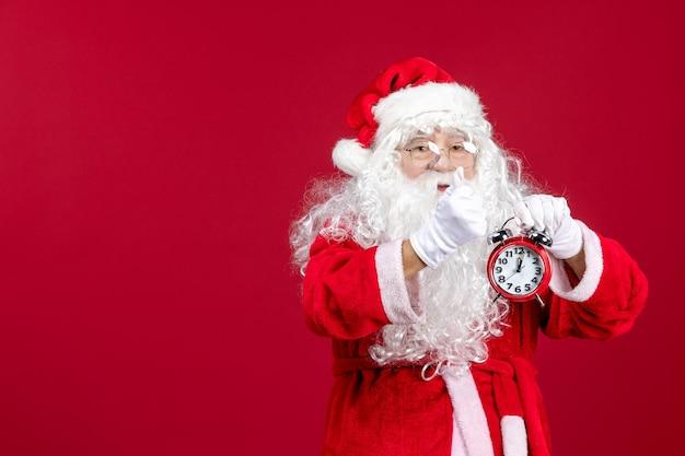 赤いクリスマスの休日に時計を保持している正面図サンタクロース