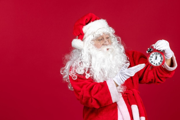 Front view santa claus holding clock on red xmas holiday new year emotion time