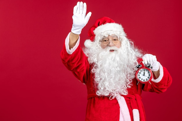 Front view santa claus holding clock on red xmas holiday new year emotions