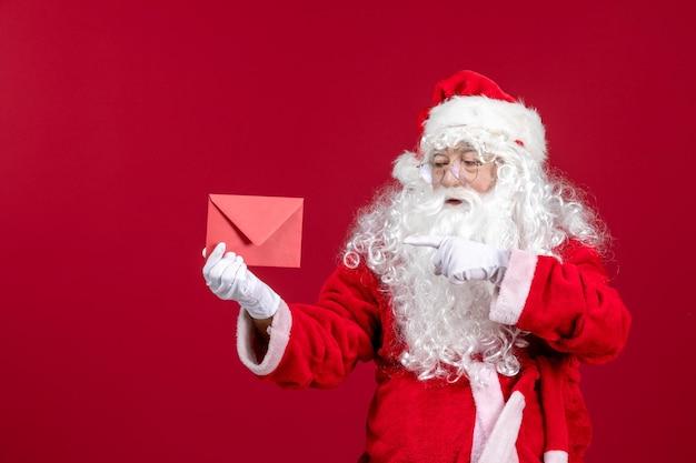 Vista frontale babbo natale che tiene busta con lettera di auguri da bambino su emozione rossa regalo di capodanno vacanze di natale