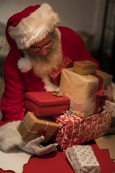 Front view santa claus holding gift boxes