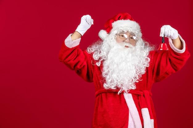 Вид спереди санта-клауса с колокольчиком на красном рождественском новогоднем подарке эмоция праздник