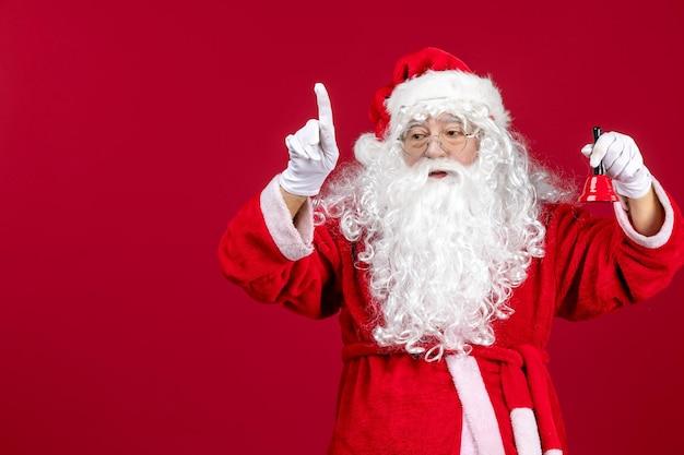 赤い床に小さな鐘を保持している正面のサンタクロースクリスマス新年の感情の休日