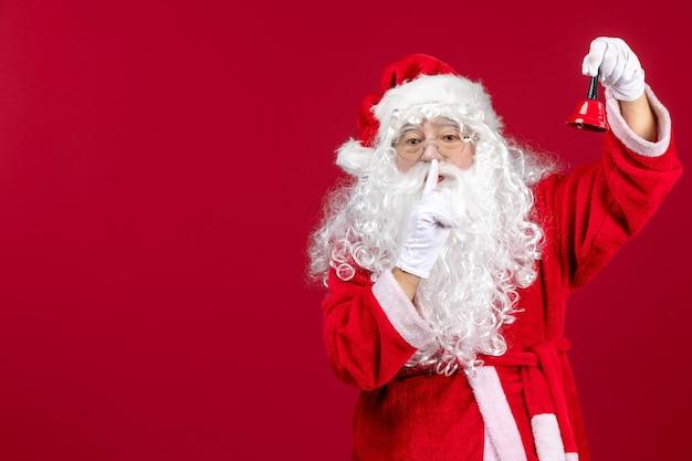 赤い贈り物の感情に小さな鐘を保持している正面のサンタクロースクリスマスホリデー新年
