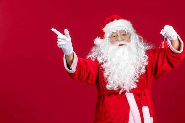 赤い贈り物の感情のクリスマスの新年の休日に小さな鐘を保持している正面のサンタクロース