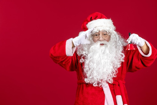 赤いクリスマスの新年の感情の休日に小さな鐘を保持している正面のサンタクロース