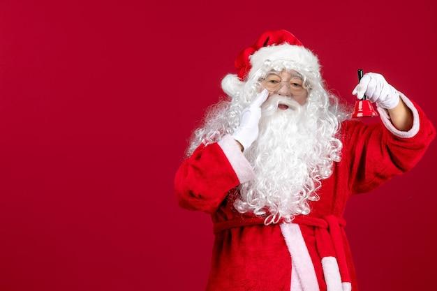 赤いクリスマスの新年の贈り物の感情の休日に小さな鐘を保持している正面のサンタクロース