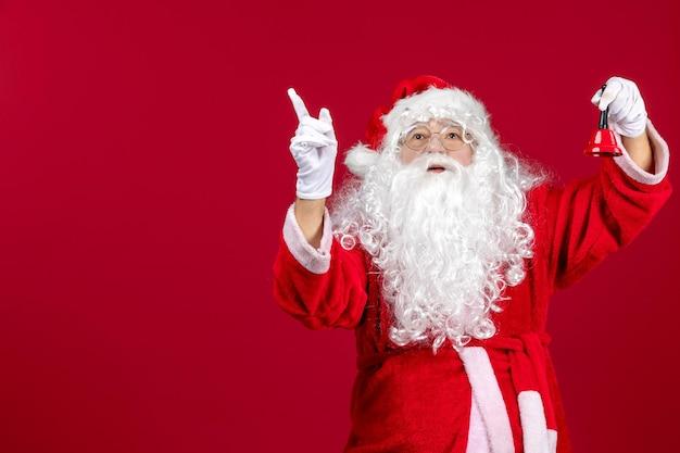 Vista frontale babbo natale che tiene un campanello sul regalo rosso emozione natale festa di capodanno