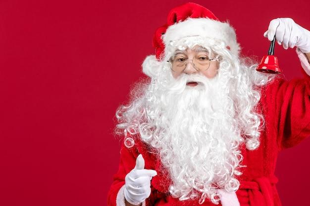 Vista frontale babbo natale che tiene una campanella sulla vacanza rossa di emozione del regalo di capodanno di natale