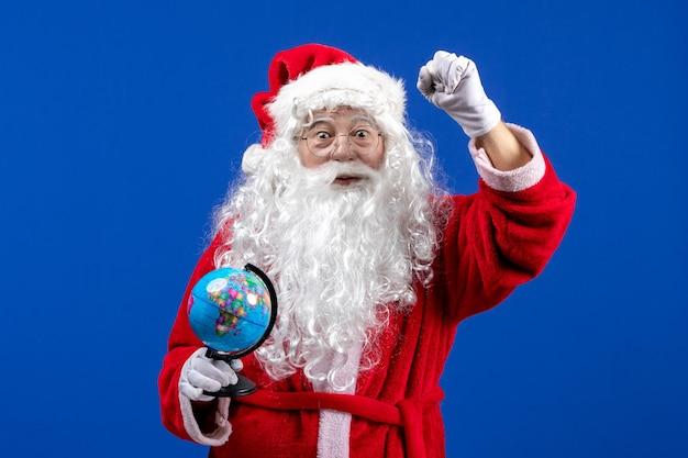 Vista frontale babbo natale che tiene un piccolo globo terrestre sulla scrivania blu colore vacanze natale capodanno