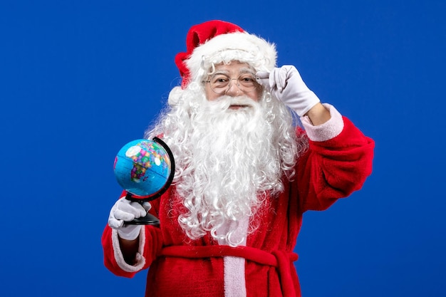 Vista frontale babbo natale che tiene un piccolo globo terrestre durante le vacanze di natale di colore blu del capodanno