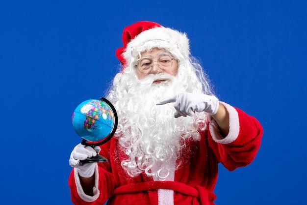 Vista frontale babbo natale che tiene un piccolo globo terrestre durante le vacanze di natale di colore blu capodanno