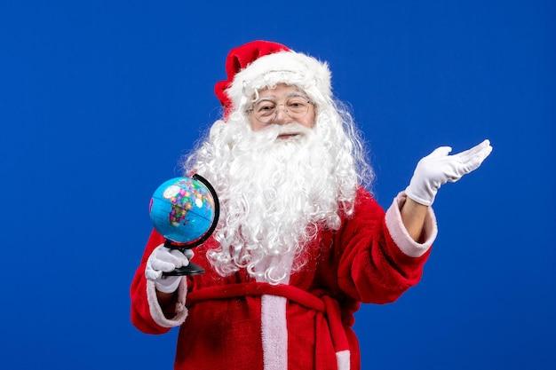 Vista frontale babbo natale che tiene un piccolo globo terrestre sui colori blu del capodanno vacanze di natale