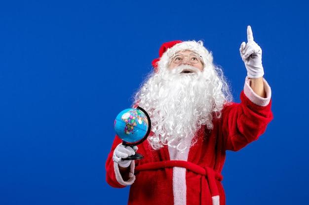 青い色のクリスマス休暇新年に小さな地球儀を保持している正面のサンタクロース