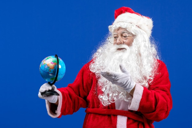青い新年の雪の色の休日のクリスマスに小さな地球儀を保持している正面のサンタクロース