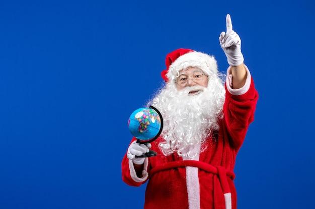 青い色の小さな地球儀を保持している正面のサンタクロースクリスマス休暇新年
