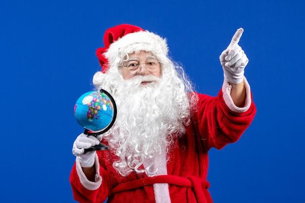 파란색 책상에 작은 지구 글로브를 들고 전면 보기 산타 클로스 새해 색상 휴일 크리스마스