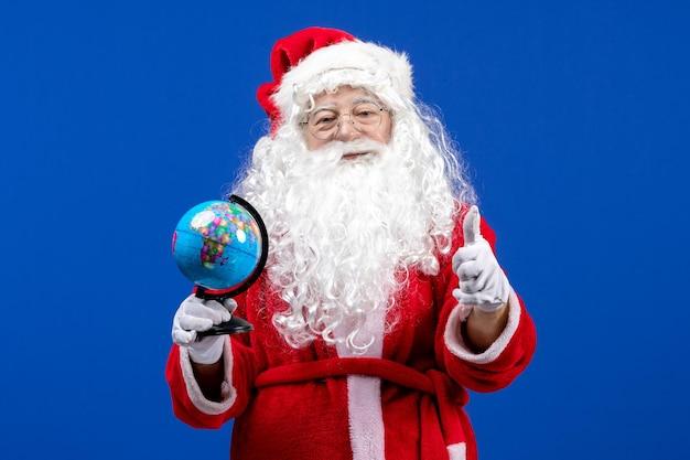 青い新年の色のクリスマス休暇に小さな地球儀を保持している正面のサンタクロース