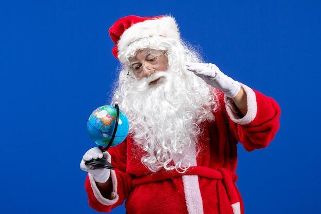 青い新年の色の休日のクリスマスに小さな地球儀を保持している正面のサンタクロース