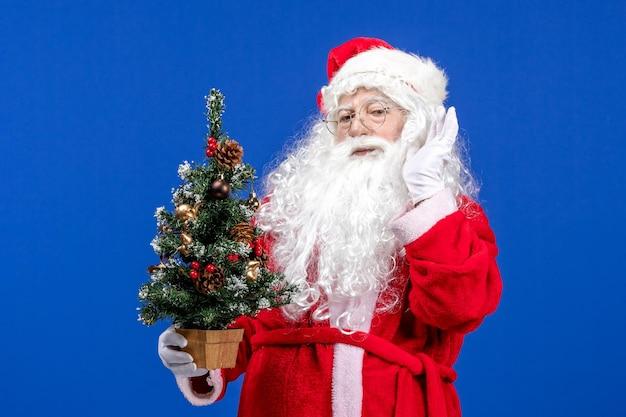 青い雪の上の小さな新年の木を保持している正面のサンタクロースクリスマス新年