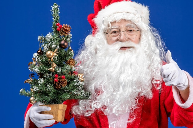 青い雪色のクリスマスに小さな新年の木を保持している正面のサンタクロース