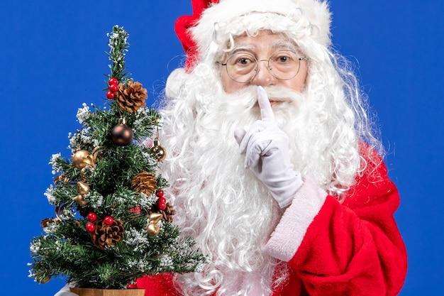 青い雪のクリスマスに小さな新年の木を保持している正面のサンタクロース