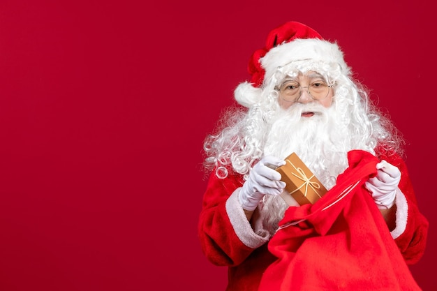 赤い床の感情の新年の子供たちへのプレゼントでいっぱいのバッグからプレゼントを保持している正面のサンタクロース