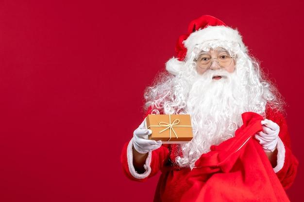 赤い新年のクリスマスに子供のためのプレゼントでいっぱいのバッグからプレゼントを保持している正面のサンタクロース