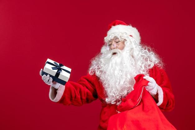 赤い新年のクリスマスの休日の感情の子供のためのプレゼントでいっぱいのバッグからプレゼントを保持している正面のサンタクロース
