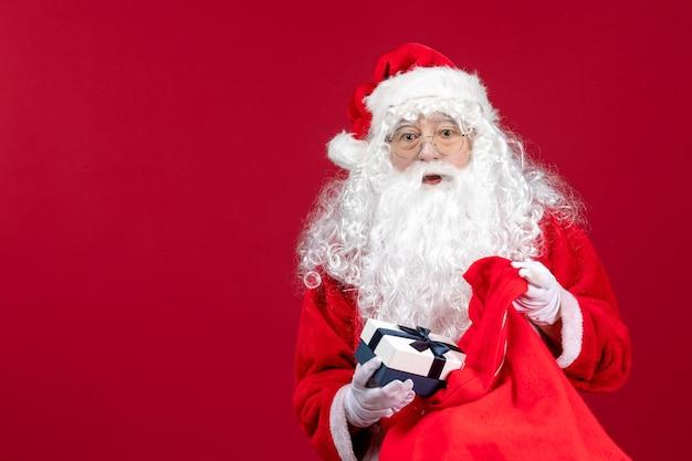 Vista frontale babbo natale che tiene presente dalla borsa piena di regali per i bambini sulla scrivania rossa capodanno emozione vacanza natale