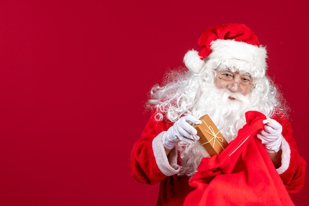 Front view santa claus holding present from bag full of presents for kids on red emotions new year