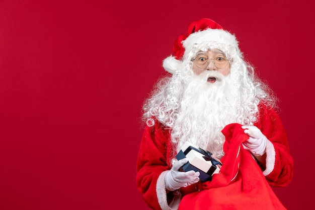 Front view santa claus holding present from bag full of presents for kids on a red new year christmas holiday emotions