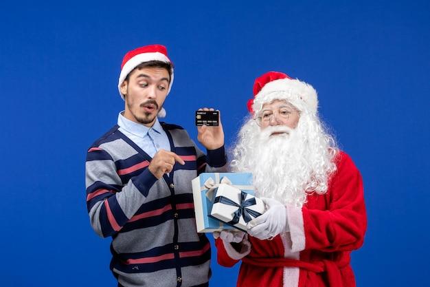 青いクリスマスの休日にプレゼントと銀行カードを保持している若い男性を保持している正面のサンタクロース
