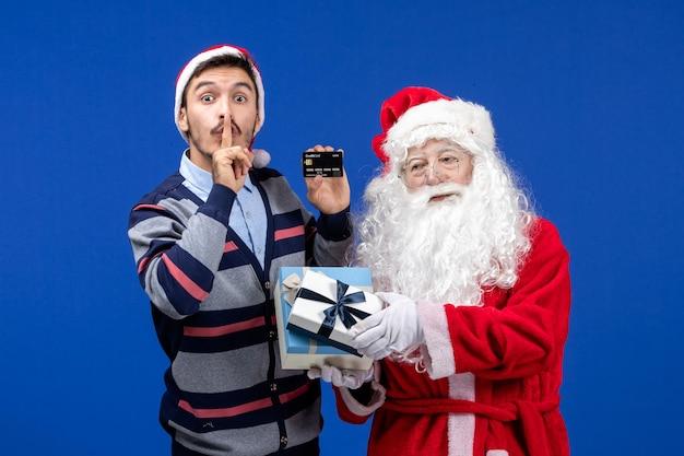 プレゼントを保持している正面図サンタクロースと青い床のクリスマス休暇で銀行カードを保持している若い男性