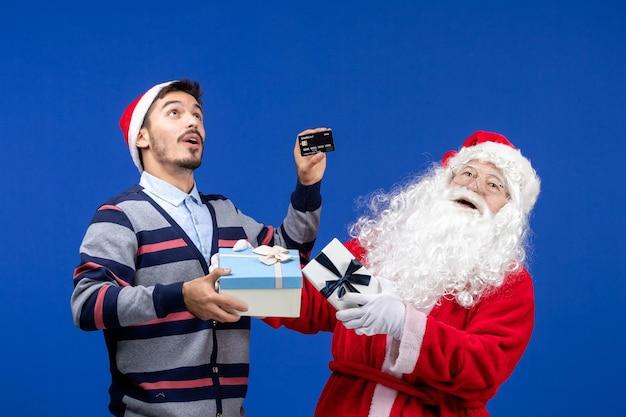 青い休日のクリスマスにプレゼントと銀行カードを保持している若い男性を保持している正面のサンタクロース