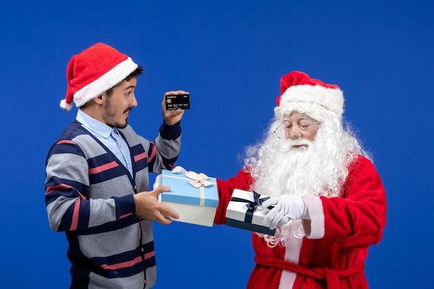 プレゼントを保持している正面図サンタクロースと青い休日のクリスマスに銀行カードを保持している若い男性