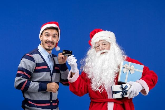 プレゼントを保持している正面図のサンタクロースと青いクリスマスの感情で銀行カードを保持している若い男性