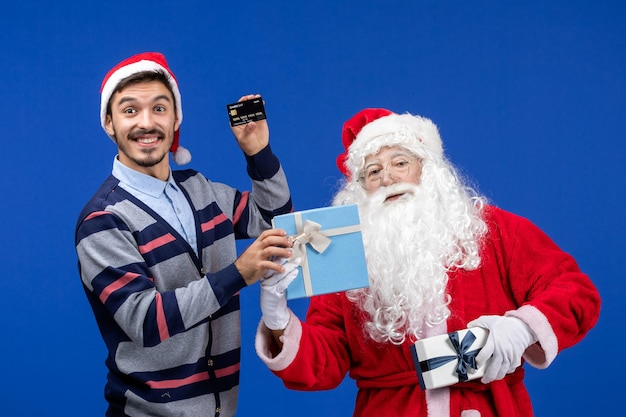 Vista frontale babbo natale che tiene i regali e giovane maschio che tiene la carta bancaria sul colore blu delle vacanze di capodanno di natale