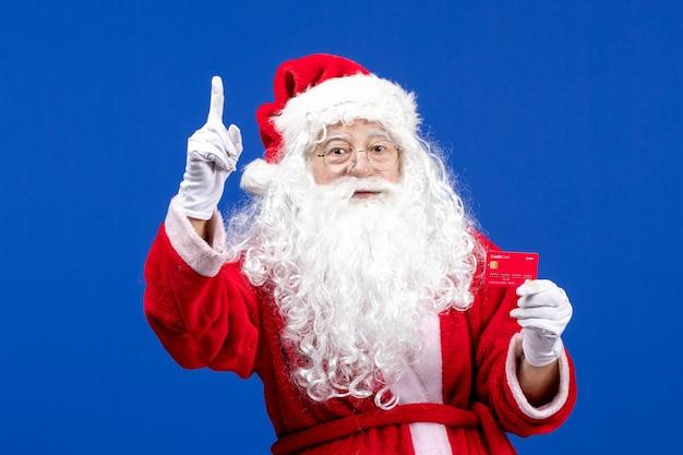 青い床に赤い銀行カードを保持している正面のサンタクロース新年の色の休日のクリスマスプレゼント