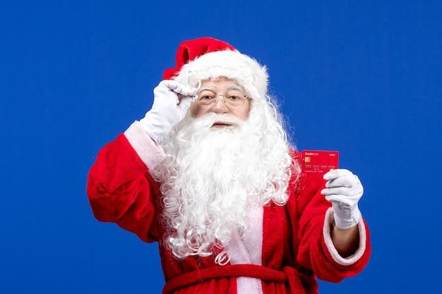 青い新年の色の休日のクリスマスプレゼントのお金に赤い銀行カードを保持している正面のサンタクロース