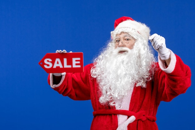 Front view santa claus holding red sale writing on the blue color snow holiday new year christmas
