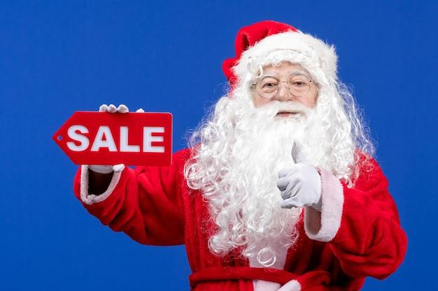 正面図サンタクロースは、青い色の雪の休日新年のクリスマスに赤いセールを書いています