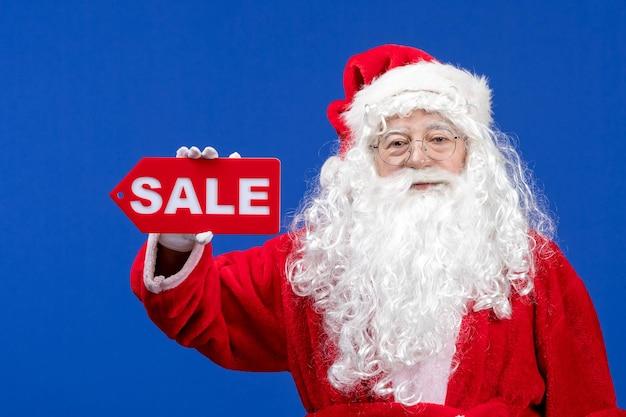 正面図サンタクロースは、青い色の雪の休日新年のクリスマスに赤いセールの書き込みサインを保持しています