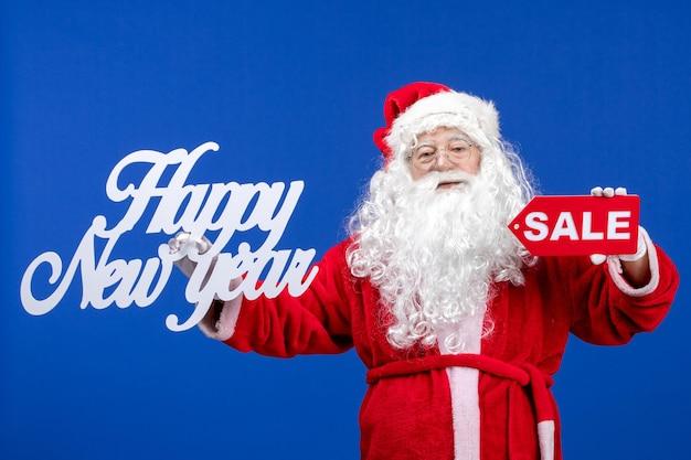 Vista frontale babbo natale che tiene vendita e felice anno nuovo scritti su colore blu neve vacanza capodanno
