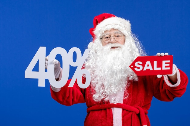 Front view santa claus holding sale and writings on blue color snow holiday new year christmas