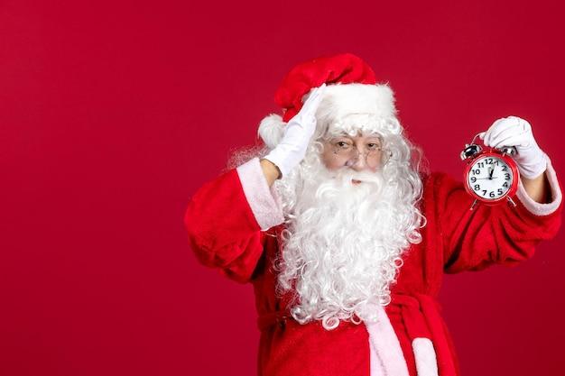 赤いクリスマスの休日の感情の時間に時計を保持している赤いスーツの正面のサンタクロース