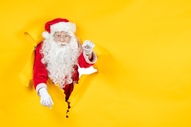Front view of santa claus looking through ripped paper yellow wall